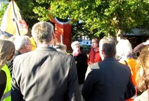 Staatssekretärin Nestle (MELUR) im roten Anorak besucht anti-Fracking-Demonstranten vor ihrer Tür